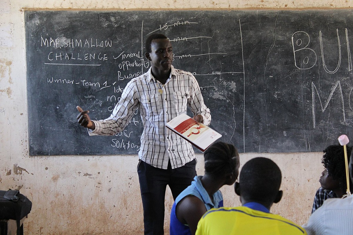 teen entrepreneur Daniel Deng in the front of a classroom in the South Sudan